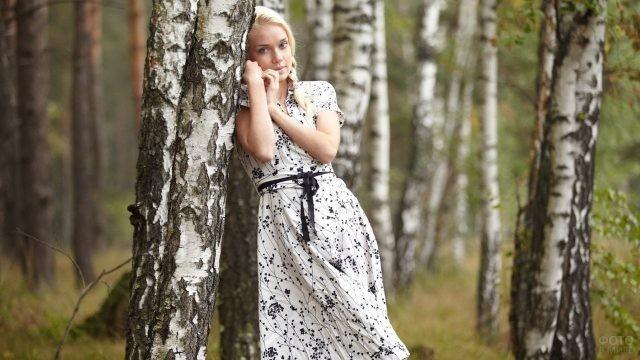 Русская девушка в сарафане рядом с берёзкой
