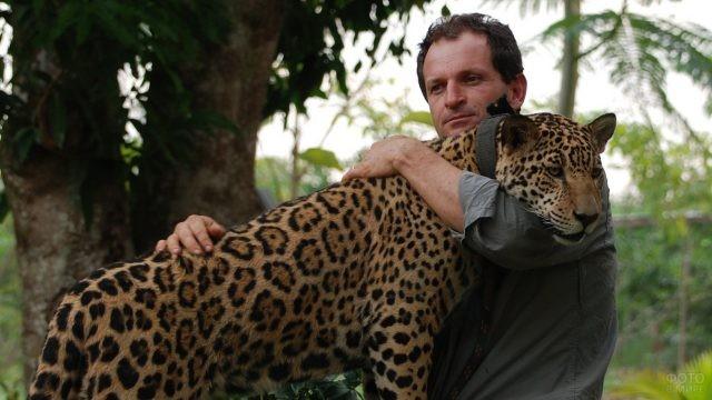 Мужчина обнимает ягуара