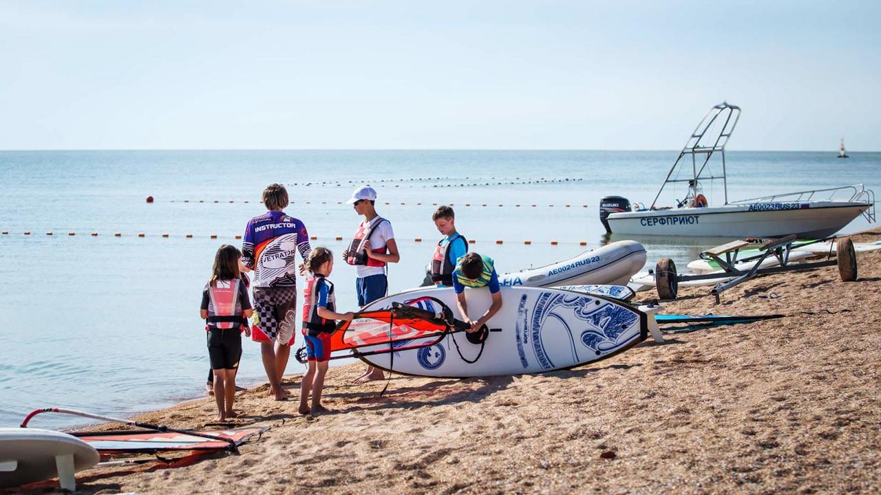 Дети на пляже на уроке виндсёрфинга