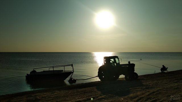 Трактор вытаскивает катер на вечерний пляж