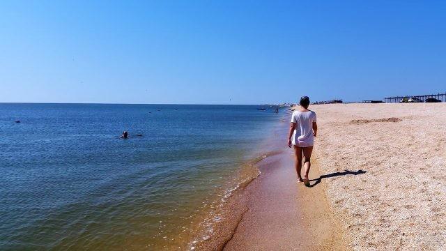 Туристка идёт по мелководью Азовского моря