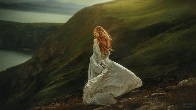 Девица в светлом длинном платье в долине гор у реки