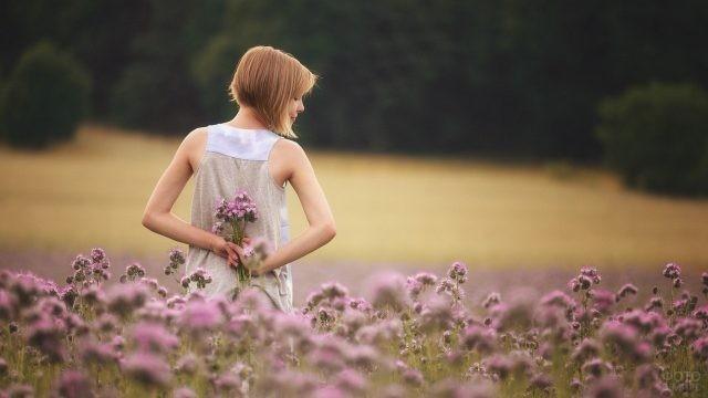 Девушка с каре прячет цветы за спиной на природе