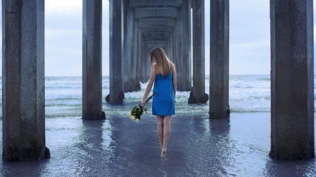 Девушка с розами идёт по воде под мостом