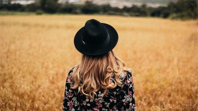 Девушка в чёрной шляпе в поле сухой травы