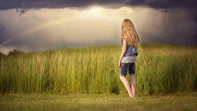 Девушка в джинсовой одежде смотрит на радугу