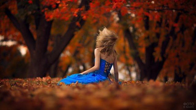 Девушка в платье на земле в осеннем парке
