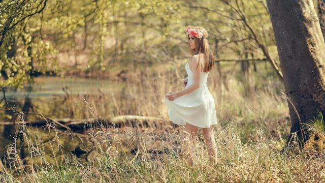 Девушка в венке из цветов в лесу