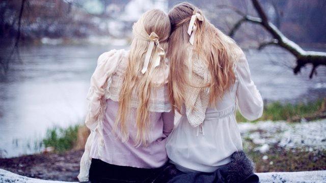 Подружки в светлых блузках на бревне у реки
