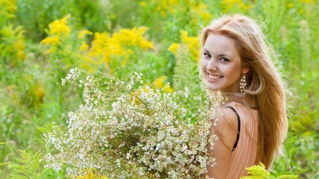 Русая девушка с букетом лечебной ромашки на природе