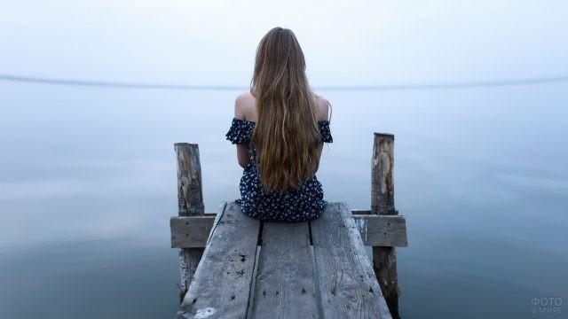 Русая девушка сидит на мостике у водоёма