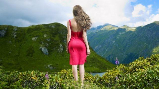 Русая девушка в красном платье на фоне зелёных гор