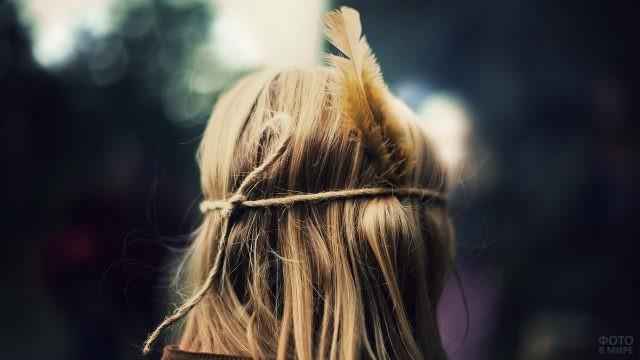 Русые волосы девушки перевязаны верёвкой с пером
