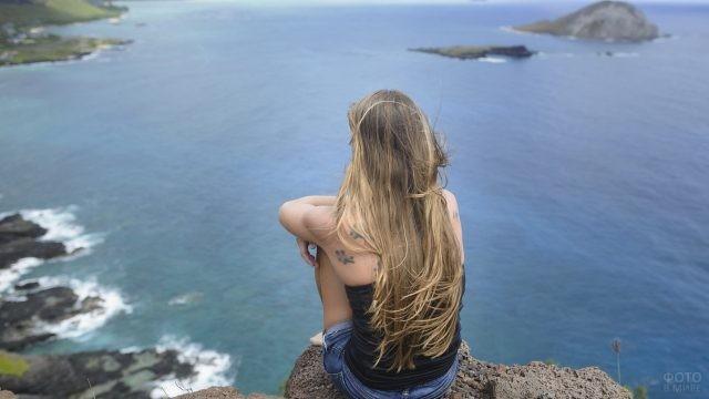 Смелая девушка на вершине горы у моря
