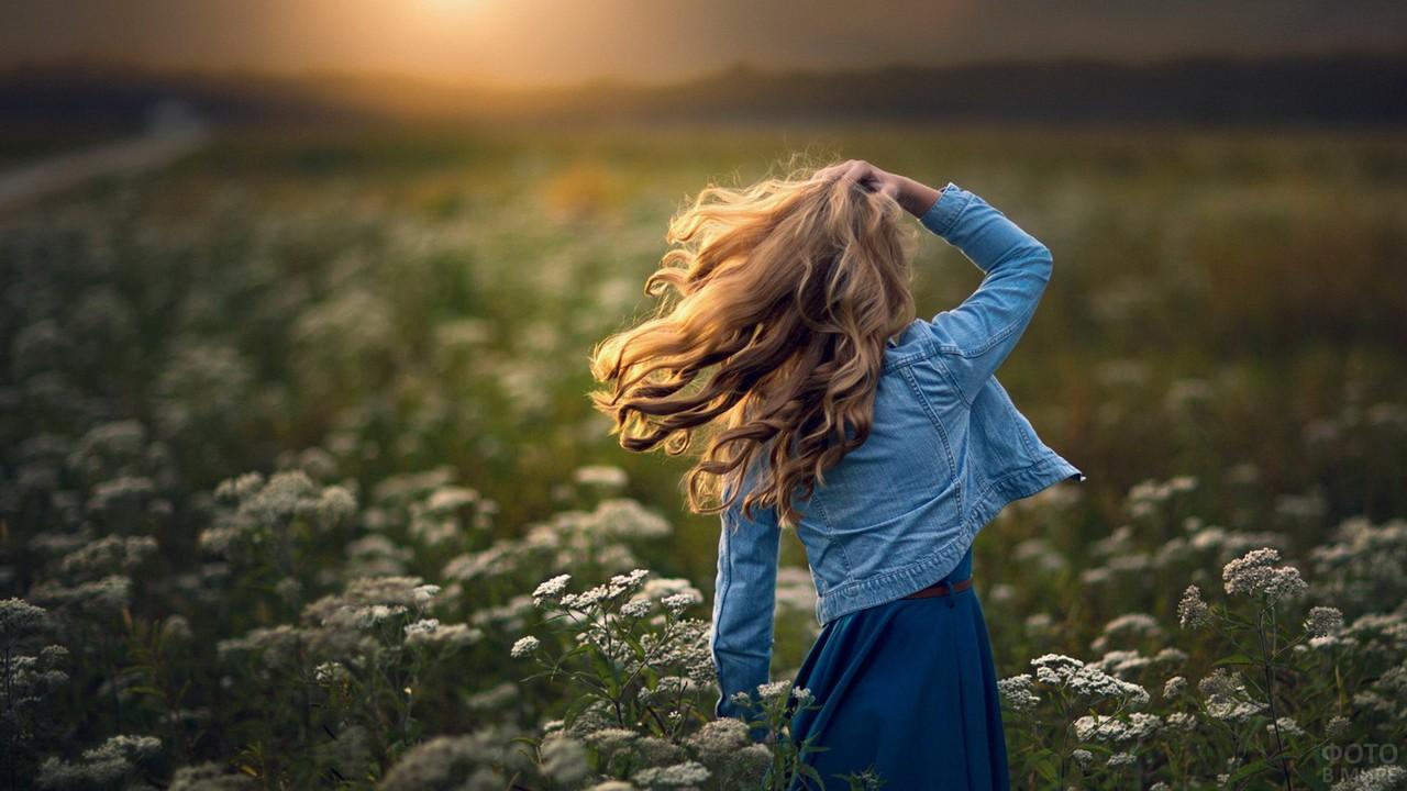 Весёлая девушка в джинсовке на лугу полевых цветов