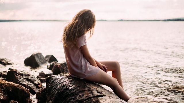 Задумчивая девушка на камнях опустила ноги в море