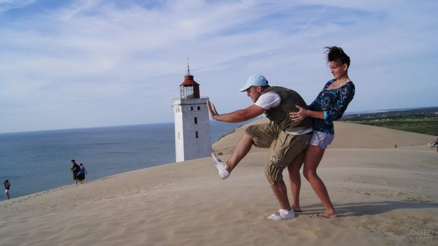 Девушка держит парня, толкающего маяк