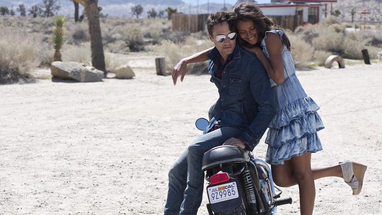 Девушка облокотилась на парня на мотоцикле