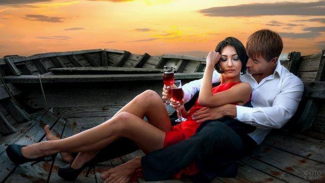 Девушка пьёт вино с парнем в лодке