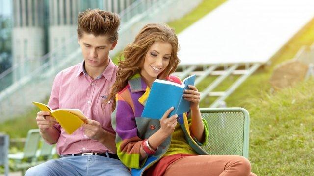 Девушка с парнем читают книги на лавочке