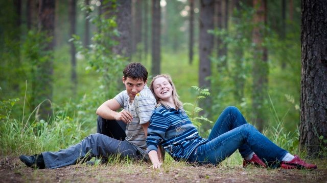 Девушка с парнем на земле в лесу