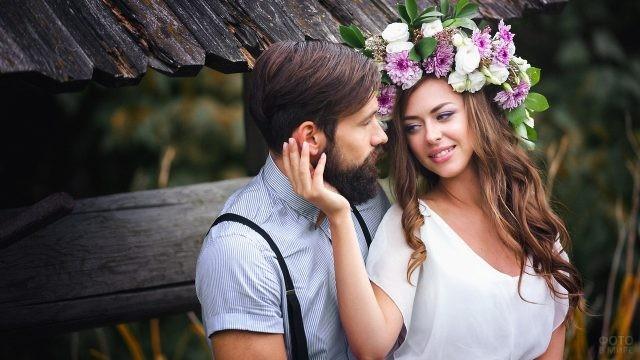 Девушка в венке с бородатым парнем возле старого колодца