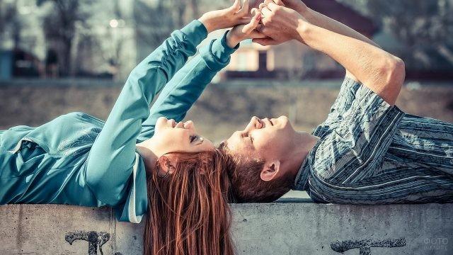 Двое на бетонном ограждении держатся за руки
