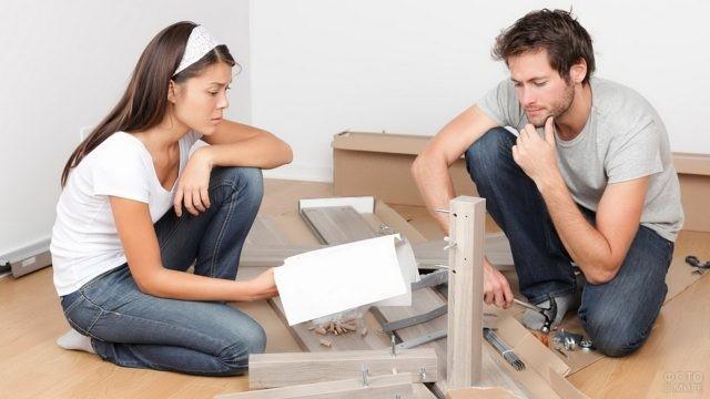 Двое собирают мебель по инструкции