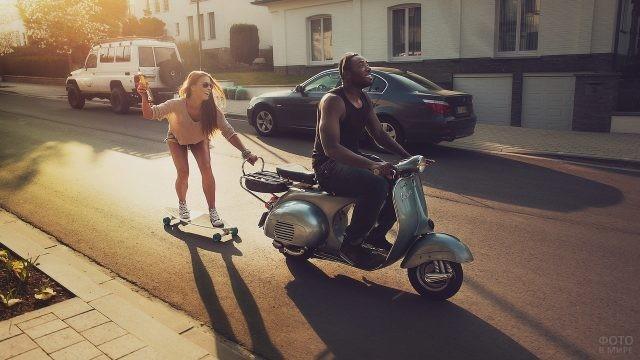 Экстремалка на скейте держится за движущийся мотороллер с водителем