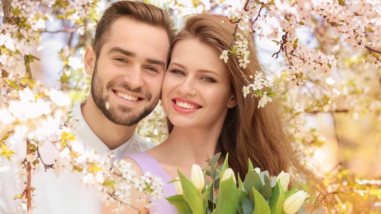 Красивая пара среди цветущих деревьев