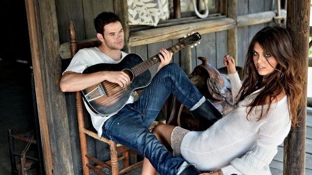 Молодой человек играет на гитаре для девушки