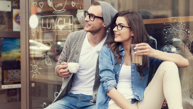 Молодые люди в очках пьют кофе