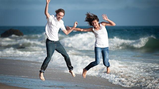 Молодые люди в прыжке на берегу моря