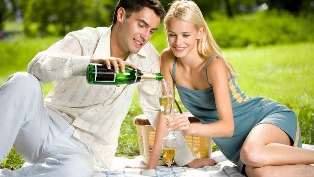 Мужчина наливает шампанское блондинке на пикнике
