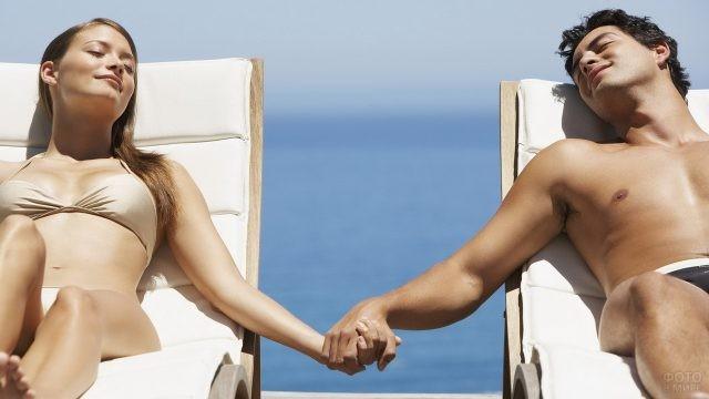 Отдыхающие на пляжных шезлонгах держатся за руки