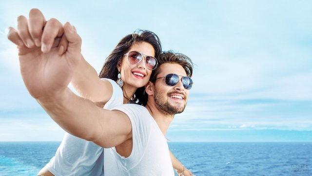 Пара в солнцезащитных очках на фоне моря