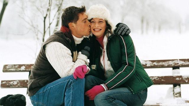 Парень целует девушку на зимней лавочке