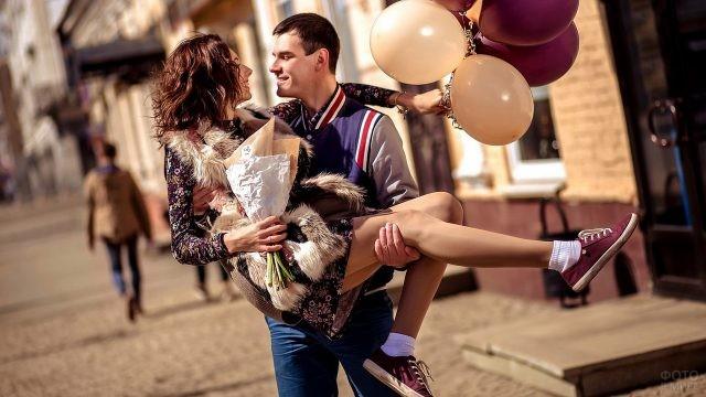 Парень держит на руках девушку с шарами