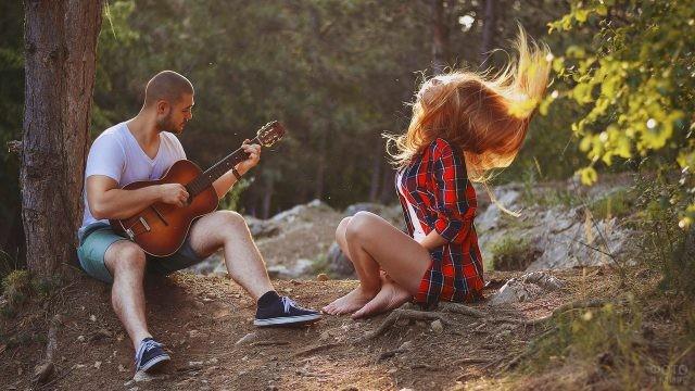 Парень играет на гитаре для рыжей девушки на природе