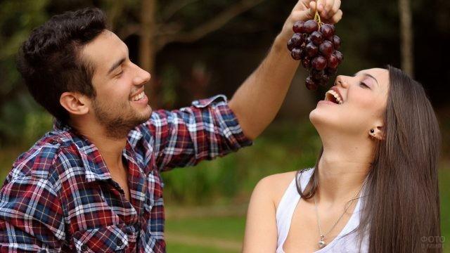 Парень кормит девушку виноградом