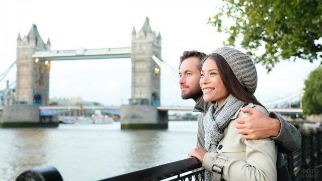 Парень обнимает девушку в берете на набережной в Лондоне