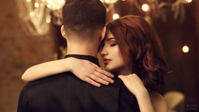 Рыжая девушка обнимает парня