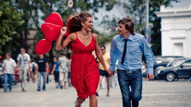 Влюблённая парочка с шарами бежит по улице