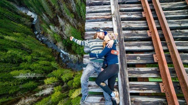 Влюблённые лежат на старой железной дороге над пропастью