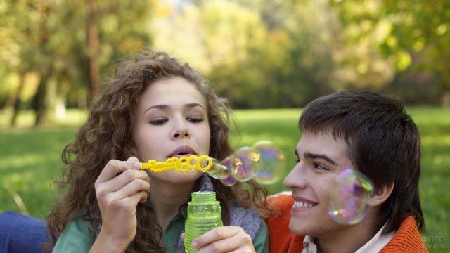 Влюблённый парень смотрит на надувающую пузыри девушку