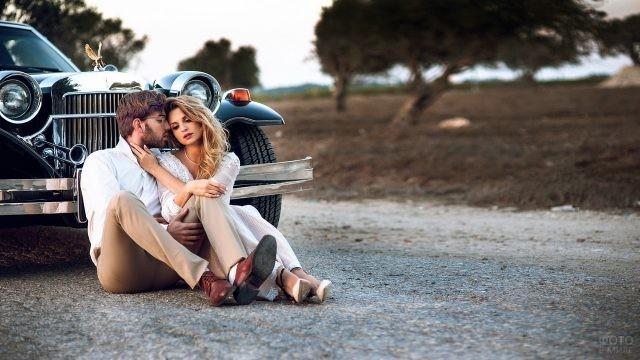 Возлюбленные сидят на дороге возле ретро автомобиля