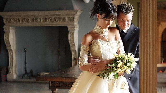 Жених обнимает невесту в красивом платье