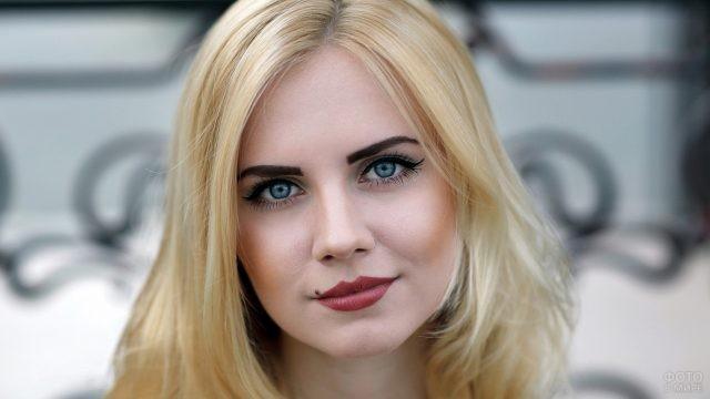 Блондинка с ярким тёмным макияжем на улице