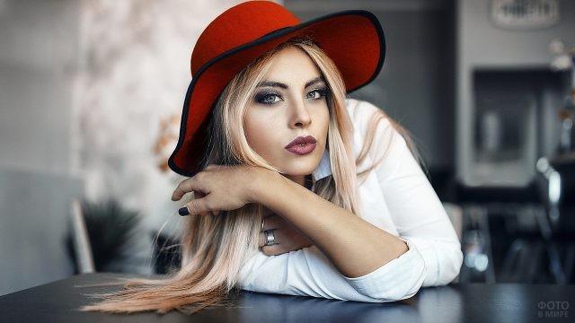 Блондинка в красной шляпе облокотилась на стол