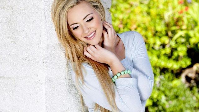 Красивая девушка у белой стены на природе